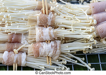 Bacon wrapped mushrooms is a street food in local market in Thailand, closeup. Thai food