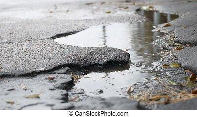 bad asphalt pit is outdoor big puddle rain road - bad...