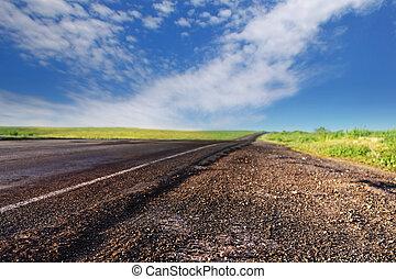 bad asphalt road in summer day