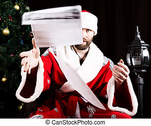 bad brutal Santa Claus discontentedly reads letter with the wishes and throwing paper, on the background of Christmas tree