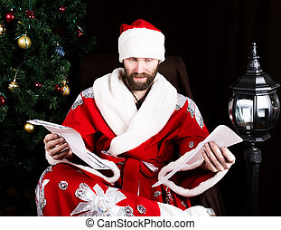 bad brutal Santa Claus discontentedly reads letter with the wishes, on the background of Christmas tree