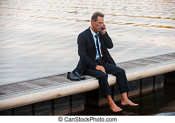 Bad business news. Depressed mature businessman talking on the mobile while sitting barefoot at the quayside