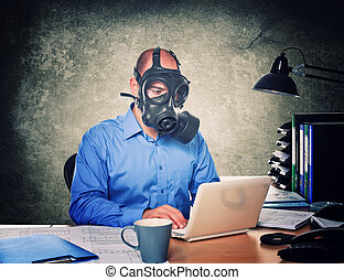 man wearing gas mask work with laptop