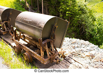 Bad Gastein, Austria - JUNE 09, 2017: Old mining truck in front of the Health resort Heilstollen, a former mining tunnel. Near Bad Gastein, Austria, Europe. Hammer and pick as symbols of mining.