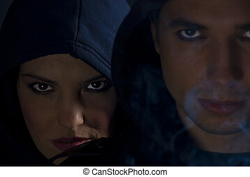 Gang members in the darkness with cigarette smoke around them, selective focus on woman face with hood, concept of bad boys urban street