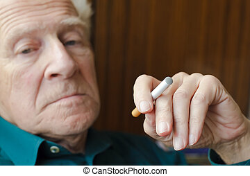 Bad Habit - close-up senior man holding electronic cigarette...