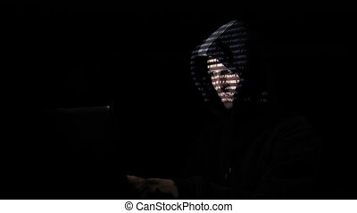 Bad hacker in hood working hard to create a virus from home...