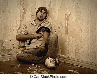 bad man - addict with a syringe using drugs sitting on the floor