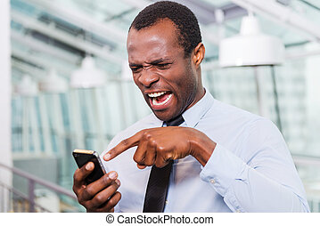 Bad news. Frustrated young African man in shirt and tie talking on the mobile phone and touching head with hand while standing indoors