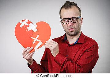 Sad adult man holding broken heart