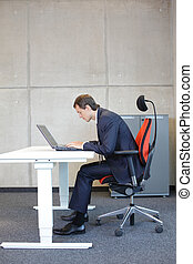 Bad sitting posture at laptop .short-sighted business man in...