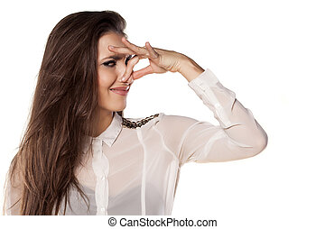 Bad smell - girl holding her nose to her toes because of the...