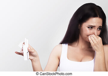 Bad smell of cigarettes. Young woman holds cigarettes in her hands. Closes hands with face. Against smoking The concept of health. On a gray background.