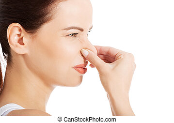 Bad smell. - Portrait of a young woman holding her nose...