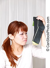 bad smell - woman holding one of socks close to her nose...