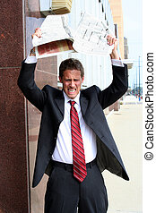 Angry businessman tearing stock pages from newspaper