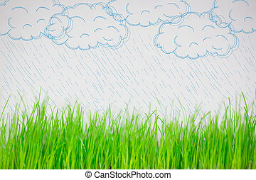 Drawing clouds and rain over spring green grass
