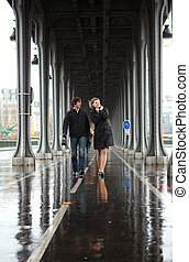 Bad weather in Paris. Couple on the Bir-Hakeim bridge at rain