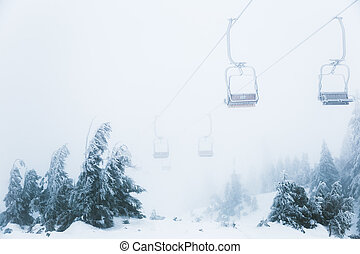 Bad weather in the ski resort lifts above the forest