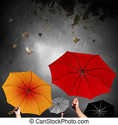 Opened umbrellas under dark sky with rain and leafs in the wind
