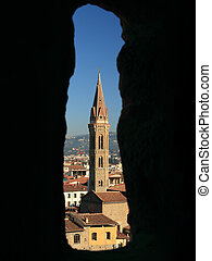 Badia Fiorentina  church seen through old stone window on tower of Palazzo Vecchio in Florence