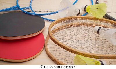 Badminton and ping pong rackets on wooden background close up. High quality FullHD footage