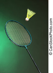 badminton racket and shuttle on green background close up