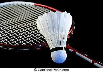 Badminton racket and shuttlecock isolated on a black...