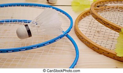 Badminton rackets and shuttlecock on wooden background close up. High quality FullHD footage