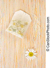 Bag of chamomile tea over wooden background - concept