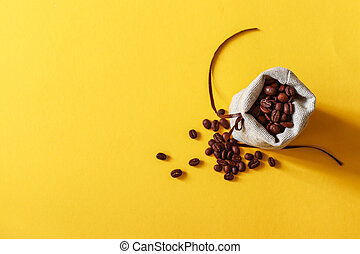 Bag of coffee beens on yellow background with copy space for your text.