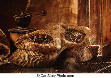 Bag of roasted coffee and coffee grinder on wooden table.