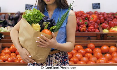 Bag of vegetables in woman's hands