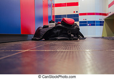Bag with fitness cloth in locker room on the floor