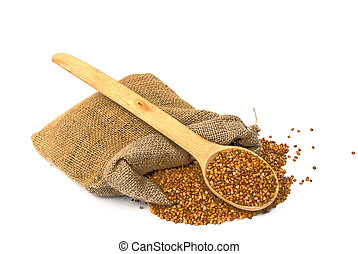 bag with scattered buckwheat and wooden spoon