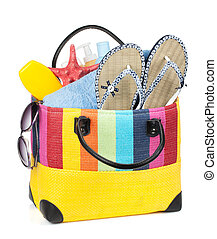 Bag with towels, sunglasses, flip-flops and beach items