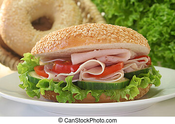 Bagel with chicken breast, slice of cucumber and tomato