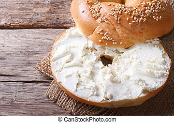 bagel with cream cheese and sesame close-up on the table. top view of the horizontal
