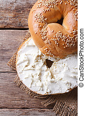 bagel with cream cheese and sesame close-up on the table. top view of the vertical