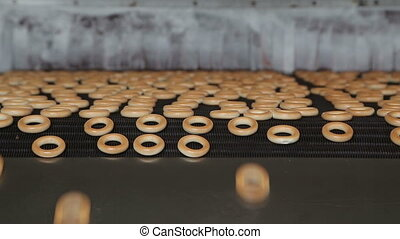 Bagels Conveyor - Freshly baked bagels are falling from the...