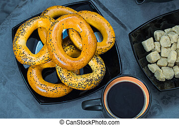 Bagels on a black plate with a dark cup of coffee and sugar on a blue tablecloth