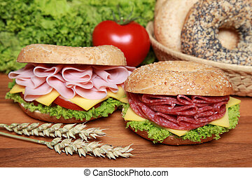 Two fresh bagels with salami and ham aswell as cheese, tomatos and lettuce