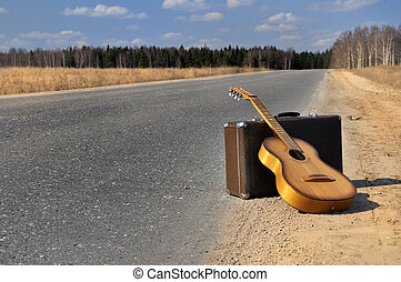 baggage and guitar on empty road - baggage and guitar lies...