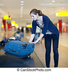 Baggage reclaim at the airport - pretty young woman taking...