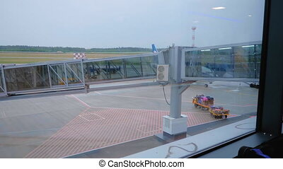 Baggage tractor with luggage drive under the airbridge in airport.