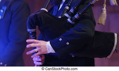 Bagpipe player plays musical instrument at the stage, close...