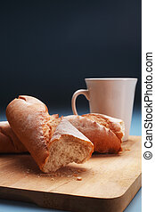 baguette on chopping board and coffee cup