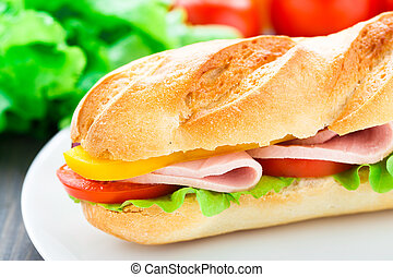 Baguette sandwich with ham, lettuce, tomatoes, pepper and onion