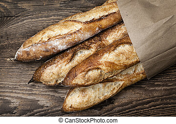 Baguettes bread - Four baguette bread loaves in paper bag on...