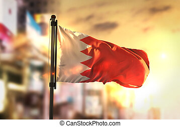 Bahrain Flag Against City Blurred Background At Sunrise Backlight